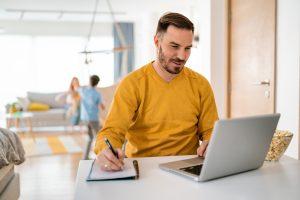 Man met baard werkt aan tafel aan laptop